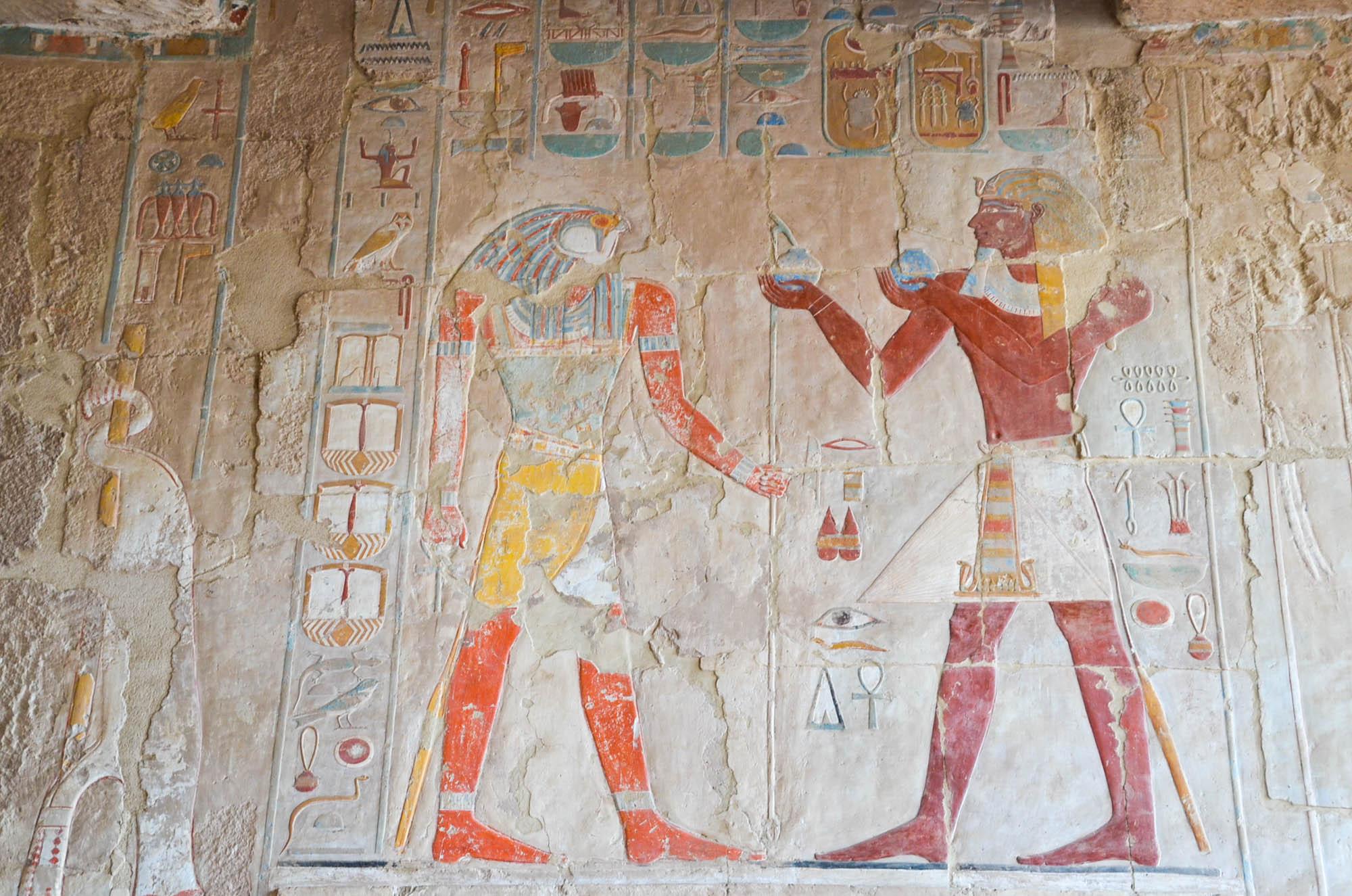 Hatschepsut, Tochter von Thutmosis I., war ägyptische Pharaonin der 18. Dynastie. Dennoch ließ sie sich immer wieder als männlicher Pharao darstellen, wie hier an den reich verzierten Wänden Ihres Totentempels, dem Gott Re Opfergaben vorlegend. Foto: Matthieu Götz